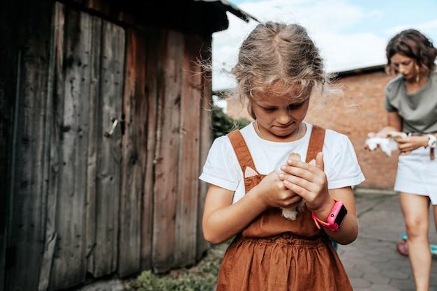 小さな子供の女の子が農場で鶏を保持しています。鶏と少女の肖像画