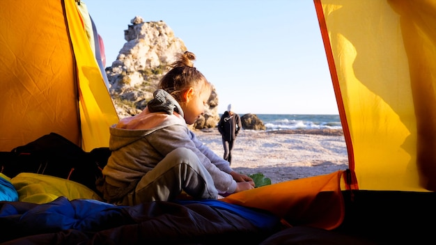 美しい朝のビーチでキャンプテントに座っている間、小さな子供の女の子は彼女の靴を置きます。