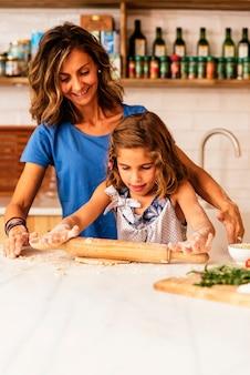 반죽을 반죽하는 어린 소녀는 쿠키를 굽기 위해 준비합니다. 유아 요리사 개념입니다.