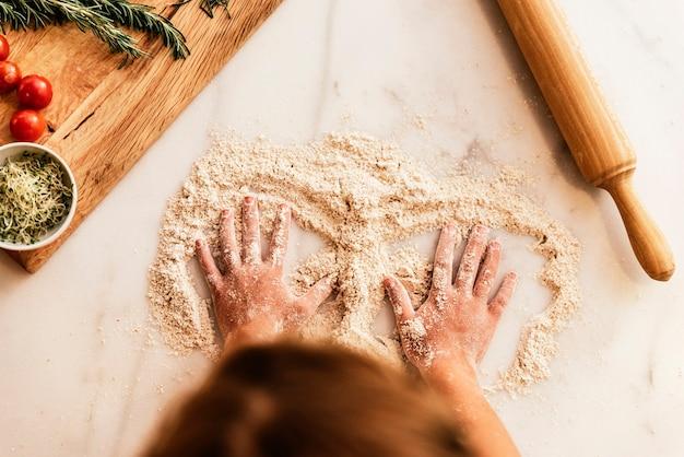 쿠키를 굽기 위해 준비하는 반죽을 반죽하는 어린 소녀. 유아 요리사 개념입니다.
