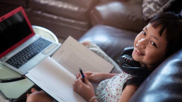 Little child girl  learning on laptop at home, online education concept