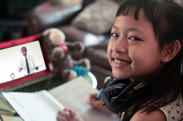 Little child girl  learning on laptop at home,social distance during quarantine, online education concept