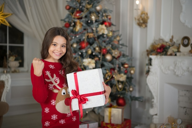 Little child girl likes xmas present. christmas. kid enjoy the holiday. happy new year. small happy girl at christmas. the morning before xmas. new year holiday. merry christmas. christmas shopping.