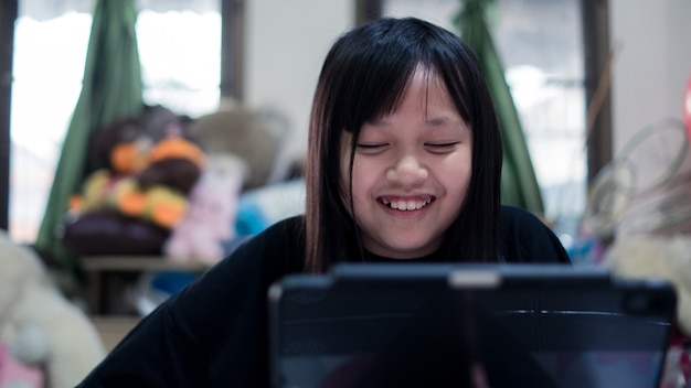 Little child  girl looking tablet distance learning class watching online lesson with funny,study in lock down as schools closed due to covid-19
