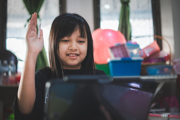 Little child  girl looking tablet distance learning class watching online lesson with raise hand up,study in lock down as schools closed due to covid-19