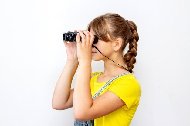 Little child girl looking through binoculars