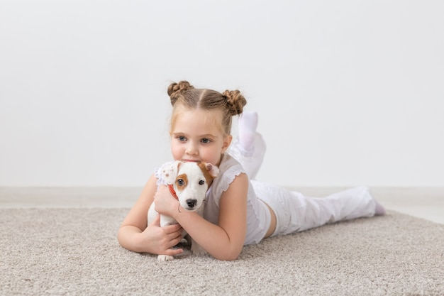 Little child girl lying on the floor with cute puppy jack