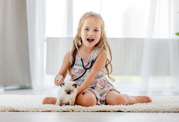실내에서 ragdoll 새끼 고양이와 수의사를 재생 하는 어린 소녀. 집에서 고양이 고양이 애완 동물의 마음을 듣는 예쁜 여자 아이
