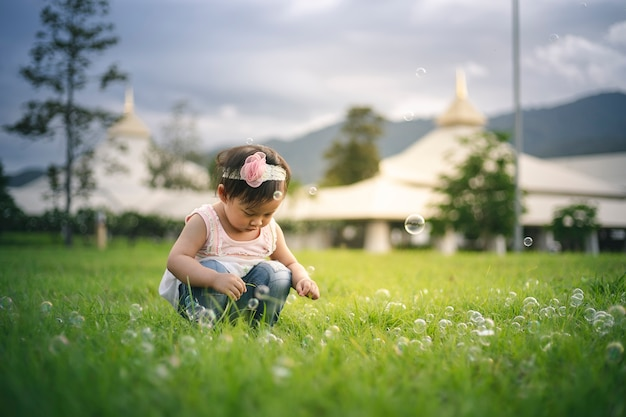 Little child girl playing with bubbles on green grass outdoors in the park.