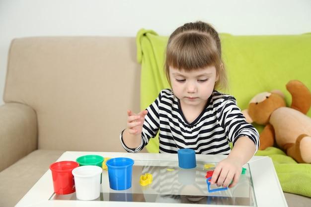 다채로운 점토를 가지고 노는 어린 아이 소녀