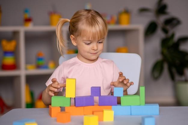 Маленькая девочка, играя в деревянные игрушки дома или в детском саду