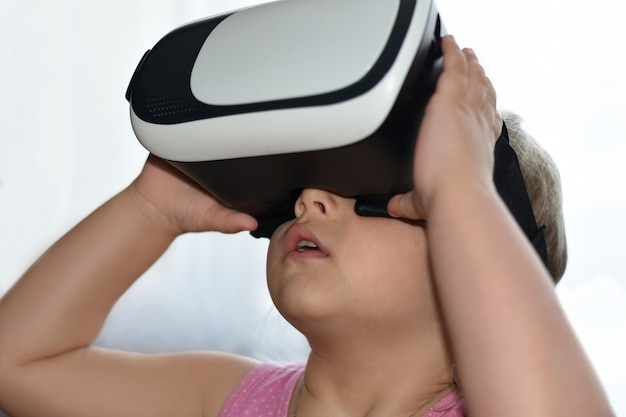 Little child girl plays a game with virtual reality glasses