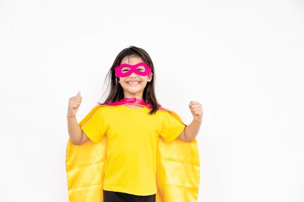 어린 소녀가 슈퍼히어로를 연기합니다. 흰색 배경에 아이입니다. 걸 파워 컨셉