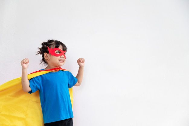 어린 소녀가 슈퍼히어로를 연기합니다. 흰색 바탕에 아이입니다. 걸 파워 컨셉