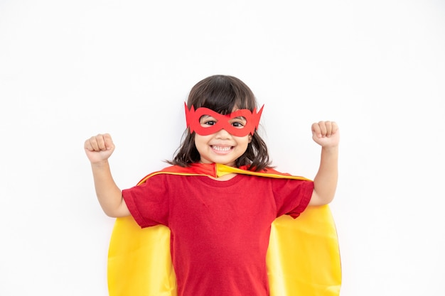 Little child girl plays superhero. child on the white background. girl power concept