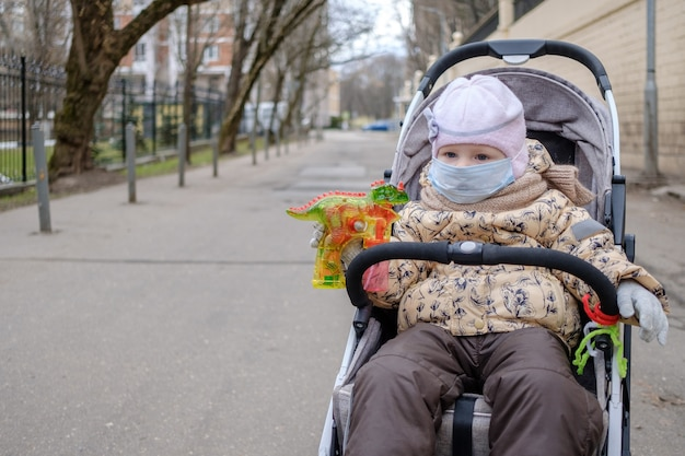 Little child girl in a protective mask on her face sits in a stroller