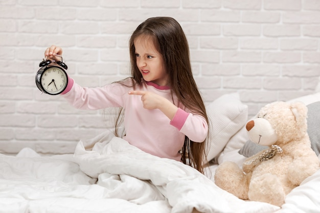 Little child girl in pyjamas with clock