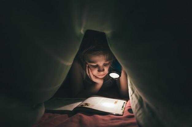 Маленькая девочка, читающая книгу с фонариком под одеялом в постели