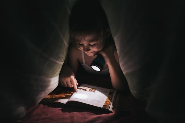 Маленькая девочка, читающая книгу с фонариком под крышкой в постели, в помещении