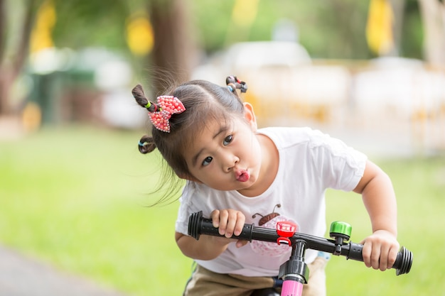 Little child girl riding bike in park