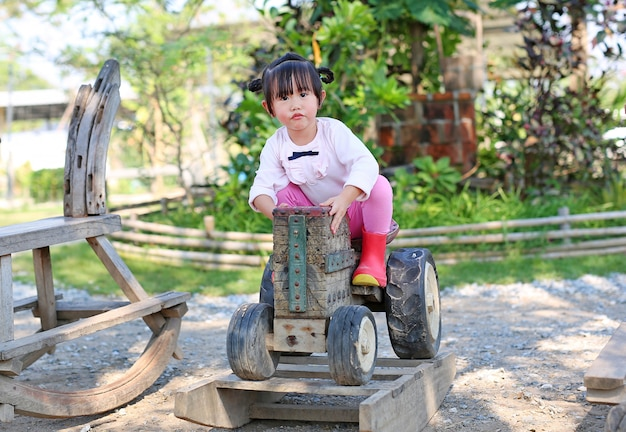 Little child girl riding on an old wooden toy tractor in the garden.