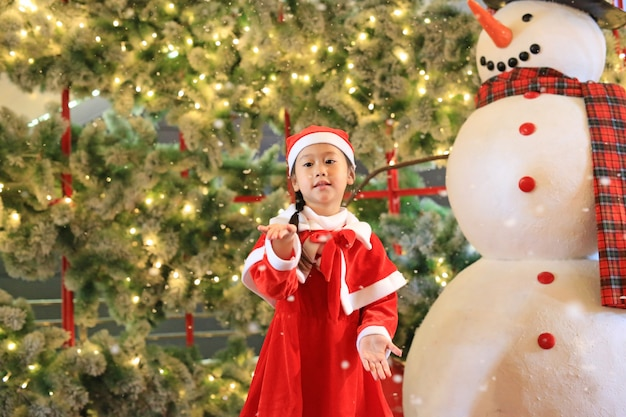 Little child girl in santa costume dress has fun and play with snow on winter time