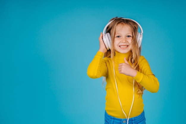 A little child girl show okay gesture and listen music in big white headphones isolated on blue background