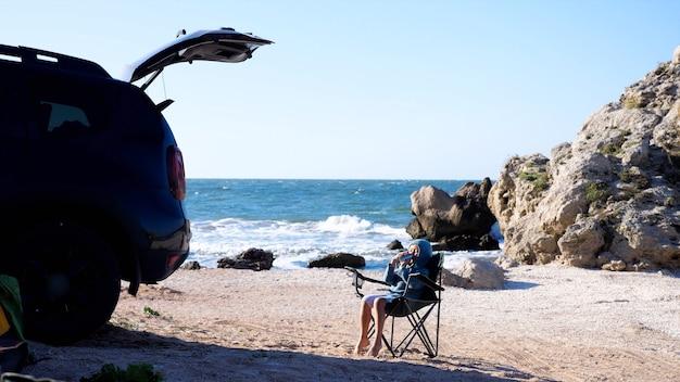 Маленькая девочка сидит на стуле и пьет из термоса рядом с кроссовером в кемпинге на пляже.