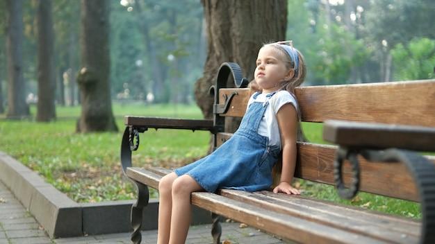 여름 공원에서 벤치에 혼자 앉아 어린 소녀.