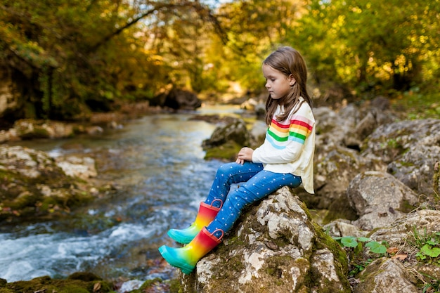 Little child girl sitting on stone near the river in the forest in rubber boots on warm autumn day. exploring nature