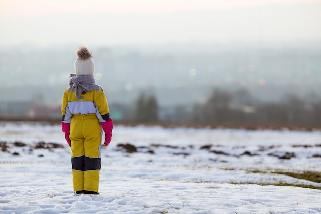 Little child girl standing outdoors alone on snow covered winter field.