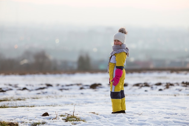 Little child girl standing outdoors alone on snow winter field.