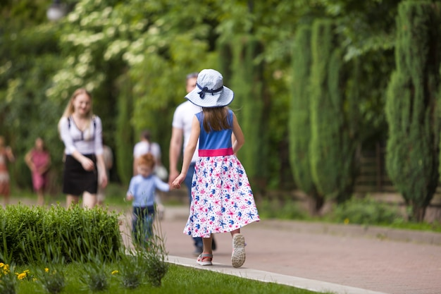 Little child girl in summer dress and a hat walking alone in green park.