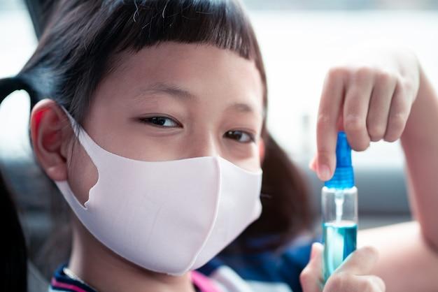 어린 아이 소녀는 얼굴 마스크를 착용하고 소독제를 들고 바이러스와 전염병 감염을 예방하고 covid-19 바이러스를 예방합니다.