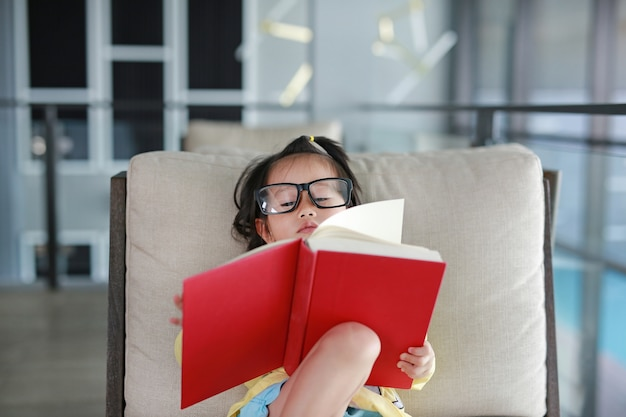 Little child girl wear glasses reading book in library
