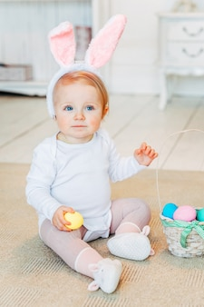 Little child girl wearing bunny ears on easter day and playing with painted eggs