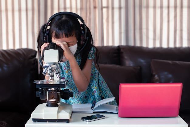Маленькая девочка девочка носить маску и наушники обучения в интернете с помощью ноутбука и микроскопа дома, дистанционное обучение