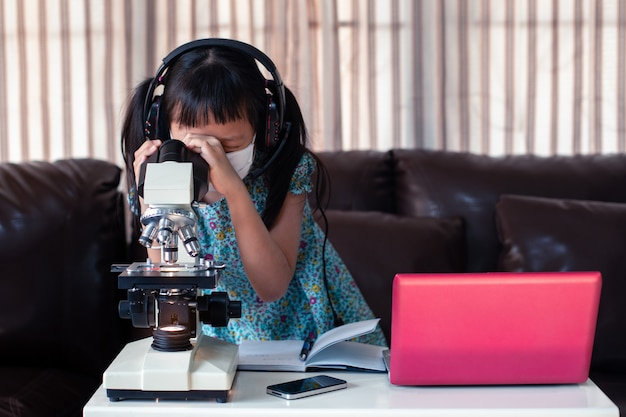 Little child  girl wearing face mask and headphones learning online by using laptop and microscope at home , distance education