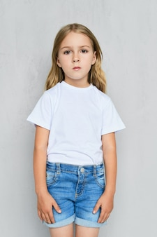 Little child girl in white t-shirt, jeans shorts and pink sneakers posing near the wall