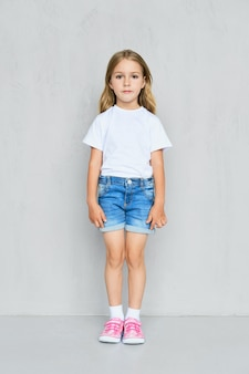 Little child girl in white t-shirt, jeans shorts and pink sneakers standing straight near the wall