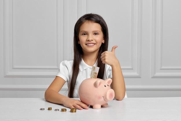 Маленькая девочка с копилкой дома