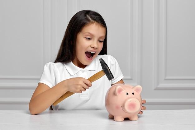 自宅で貯金箱を持つ小さな子供の女の子