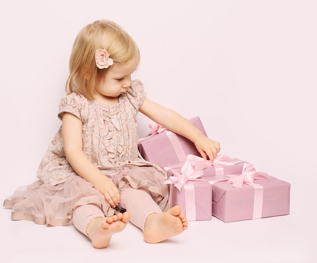 Little child girl with pink gift box birthday