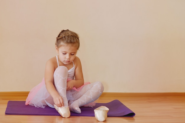Little child girl  with  pointe shoes and  pink tutu skirt