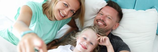 부모와 어린 아이 소녀 침대 초상화에 누워