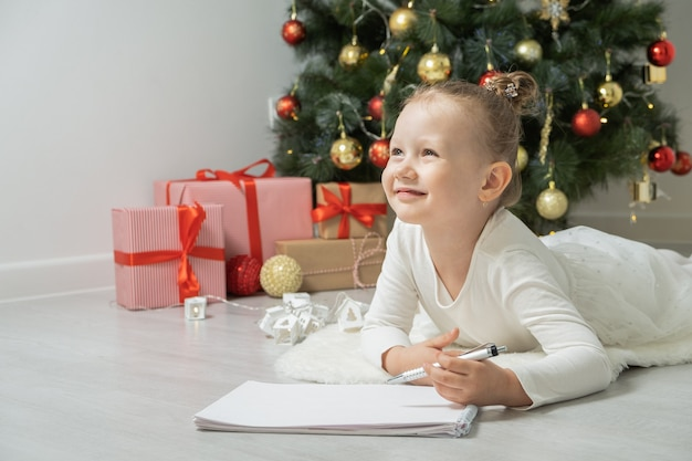 Little child girl writes letter to santa claus and dreams of a gift background christmas tree.