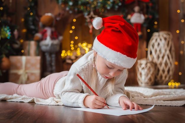 Little child girl writes letter santa claus