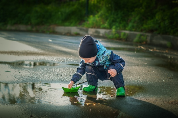 Little child in green rain boots playing with a green paper boat in a puddle