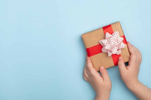 Little child hands holding a gift box on blue background