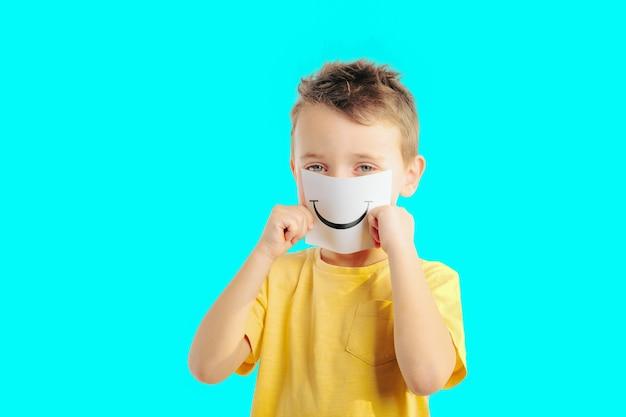Маленький ребенок держит карточку с улыбающимся лицом мальчик выбирает эмоциональные лица фото на цветном фоне